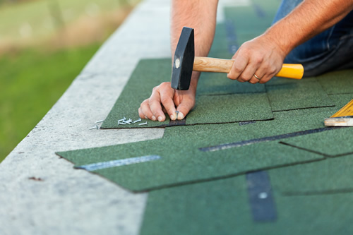 Roofing contractor laying new green asphalt roofing shingles